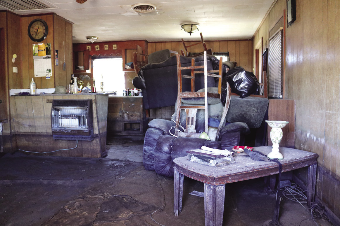 Furniture is piled inside a house severely damaged by flood water.