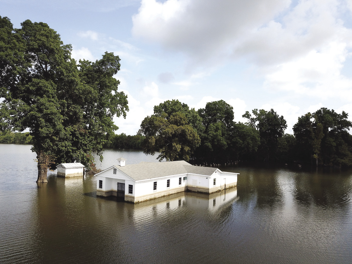 A white church building is surrounded by flood water.