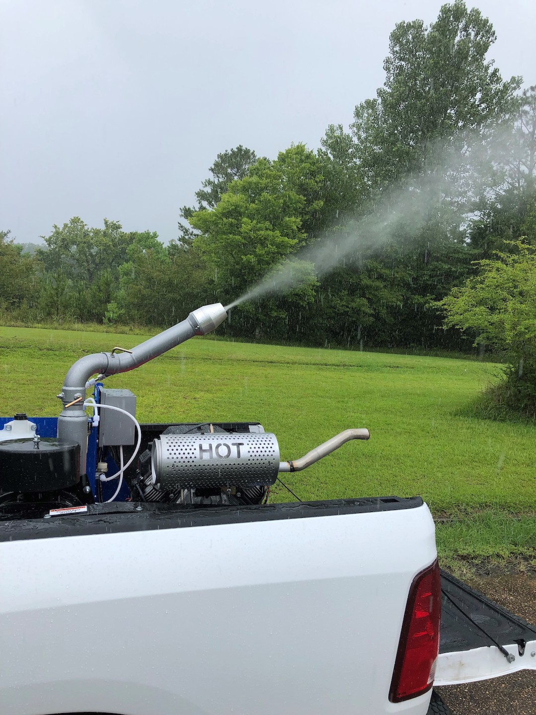 A machine in the back of a truck spraying a mist.