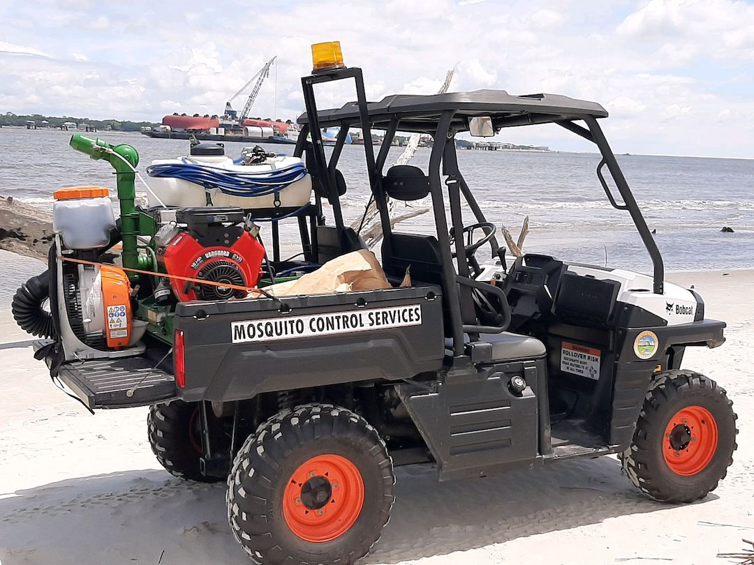 ATV on a beach with a machine to spray mosquito repellant on the back.