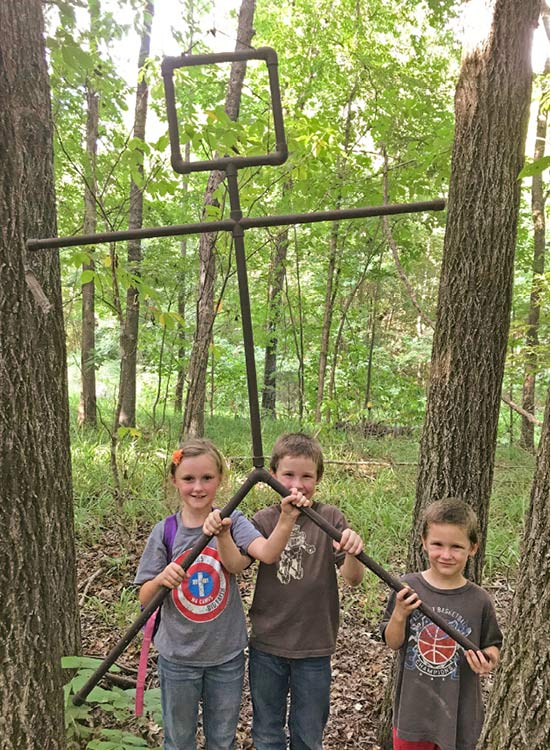 Three young children holding a large metal object that resembles a stick-figure.