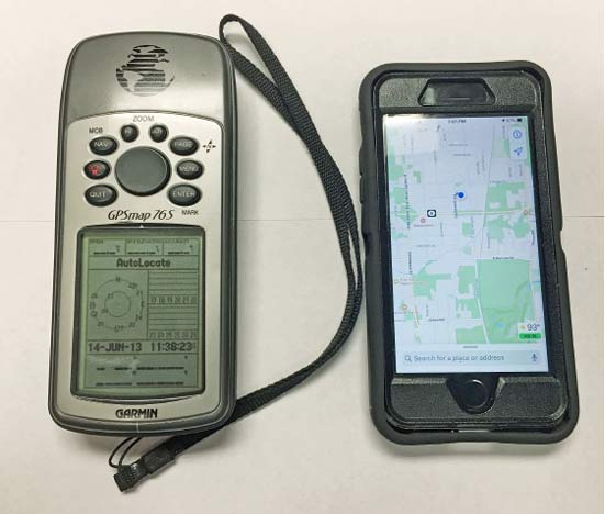 A handheld GPS unit next to an iPhone.