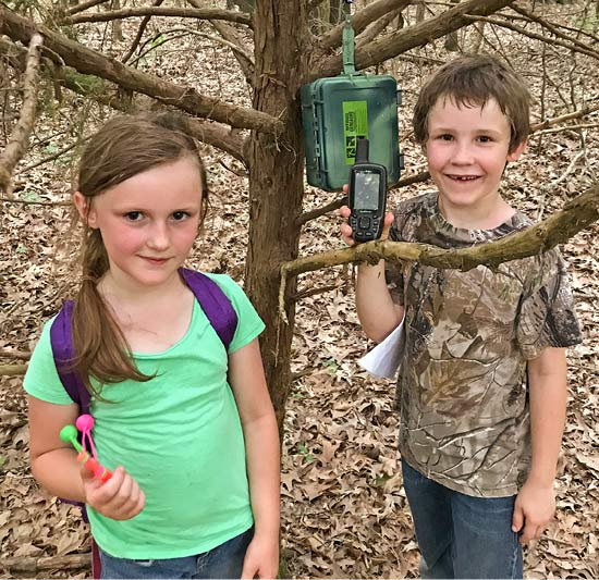 A young girl and boy holding a GPS device stand in front of a geocache hanging from a tree branch.