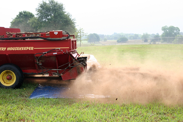 Image of a spreader spreading litter over a tarp, demonstrating the first part of step 4