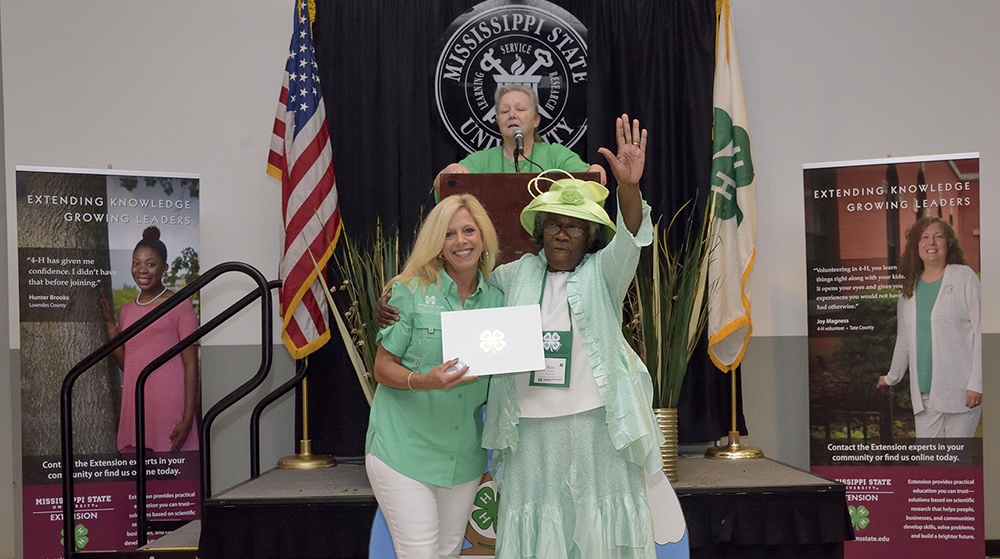 Two women, both wearing green, stand smiling in front of a podium featuring a speaker looking on.  The woman on the left holds a white folder with a silver 4-H clover emblazoned in the center.