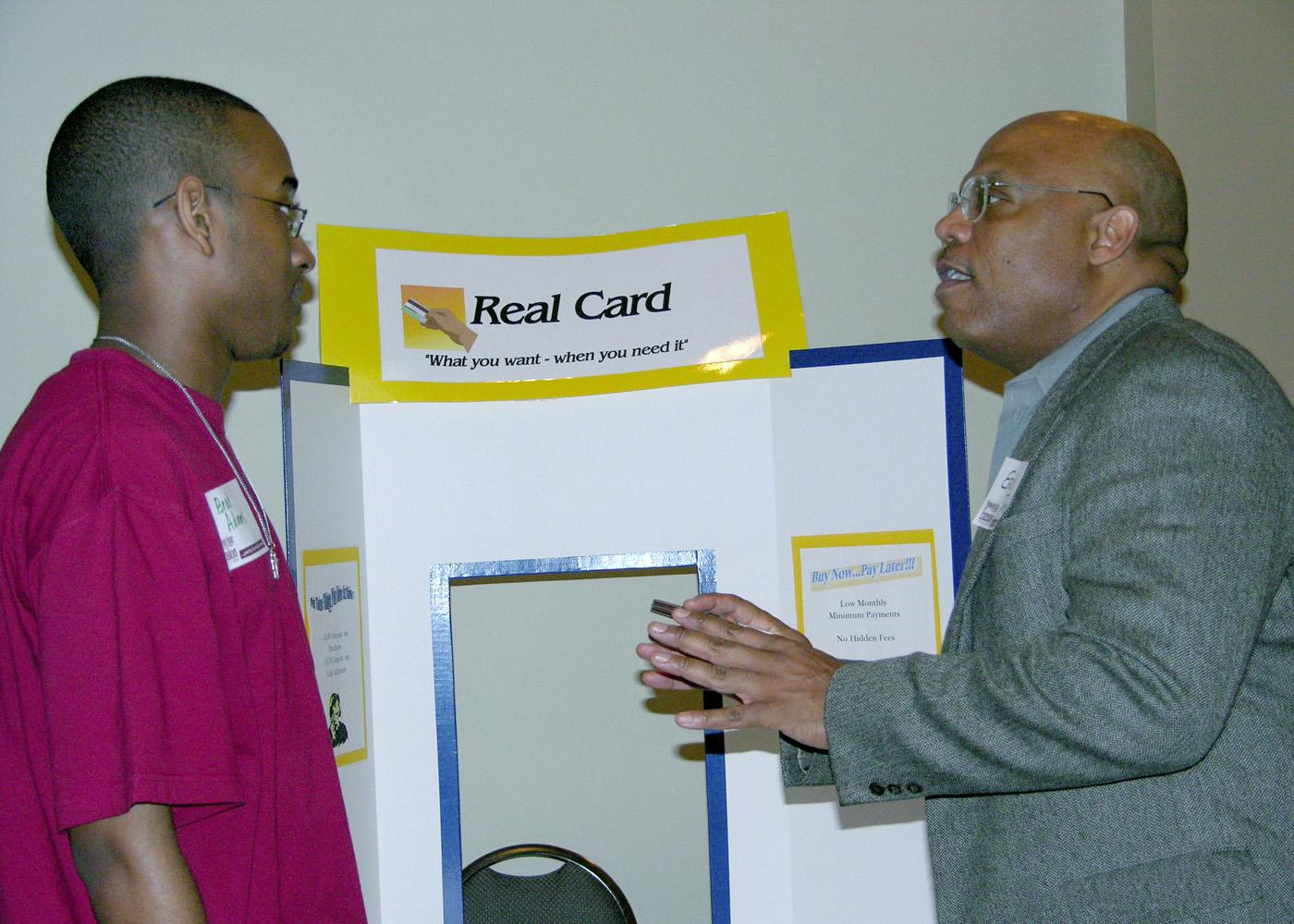 Brad Adams, a member of the Grenada High School's 4-H Leadership Club, listens to his options for a credit card from Eric Tate, playing the role of a credit card company representative in a Reality Check simulation. Tate, the director of human resources at Heatcraft in Grenada, was a resource volunteer assisting in a real-life simulation designed to enhance financial lessons.