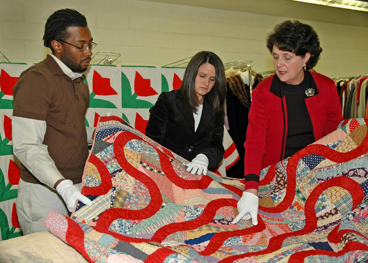 Mississippi State University students Parron Edwards (left), a junior from Lexington, and Shannon Sorro, a senior from Clarksville, Tenn., listen as Wanda Cheek, associate professor of human sciences, discusses the intricacies of quilts and their patterns.