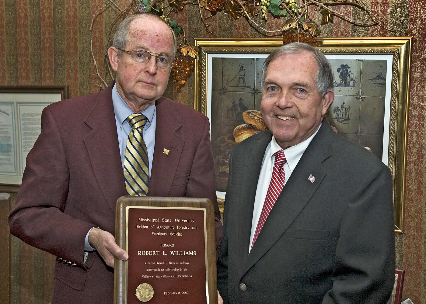MSU Vice President for Agriculture, Forestry and Veterinary Medicine Vance Watson, right, presents a plaque to Robert L. Williams recognizing the scholarship honoring the agricultural economist. (Photo by Bob Ratliff, MSU Office of Ag Communications)