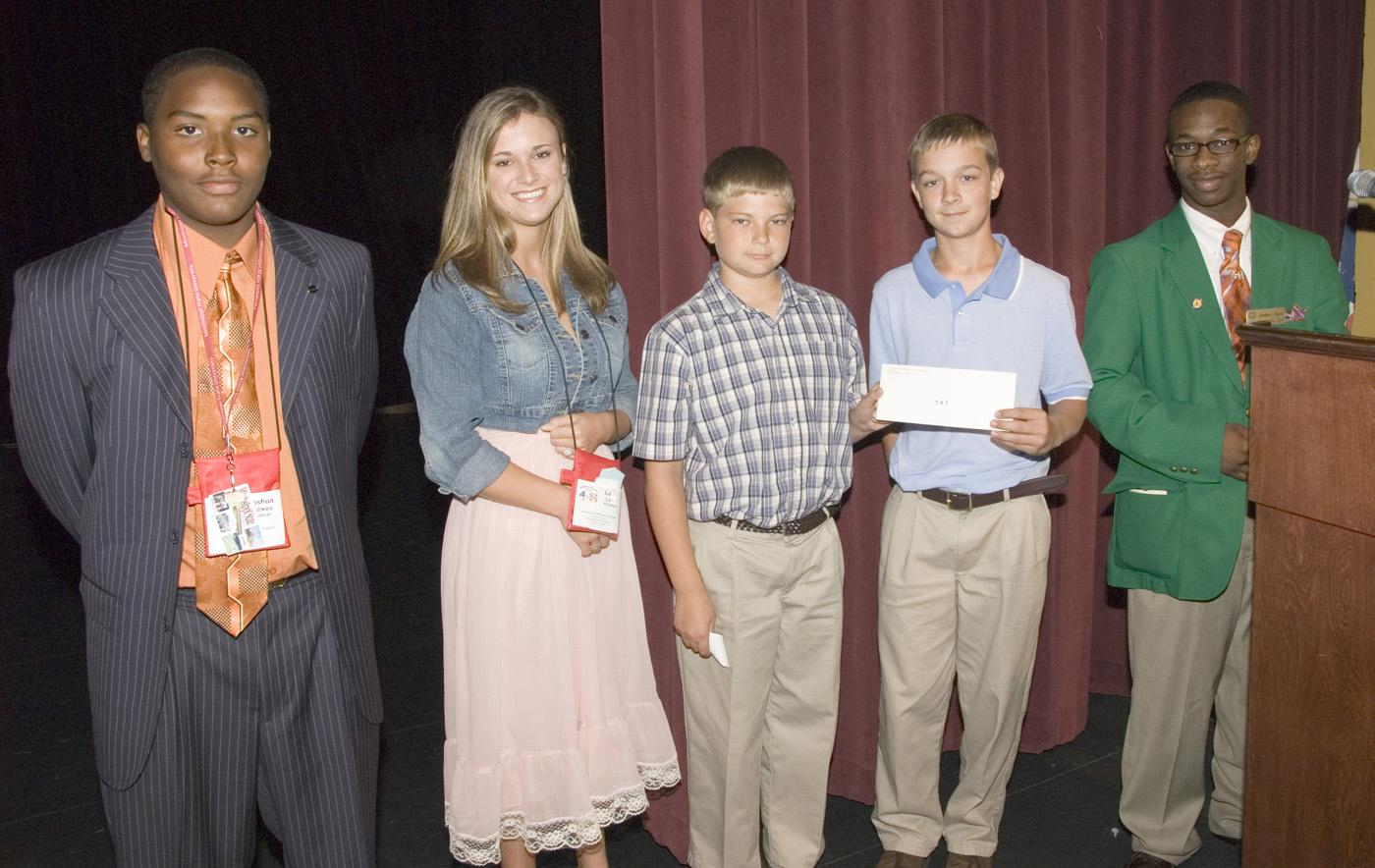 Joshua Holmes of Walthall County, from left, and Laci Lunn of Pontotoc County, represented the state's top two fund-raising counties at the 2007 4-H Congress. They presented a check to Alabama 4-H members Buddy Skipper and Ben Jones, both sixth graders from Enterprise. Leadership Team member Cord Davis of Bolivar County assisted in the presentation. (Photo by Marco Nicovich/MSU Ag Communications) Larger view.