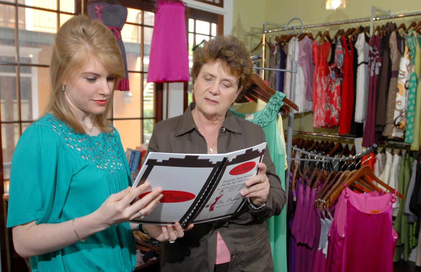 Mississippi State University senior Samantha Webb, left, of Forest, compares marketing information for a Starkville clothing store with one of her major professors, Wanda Cheek. (Photo by Jim Lytle)