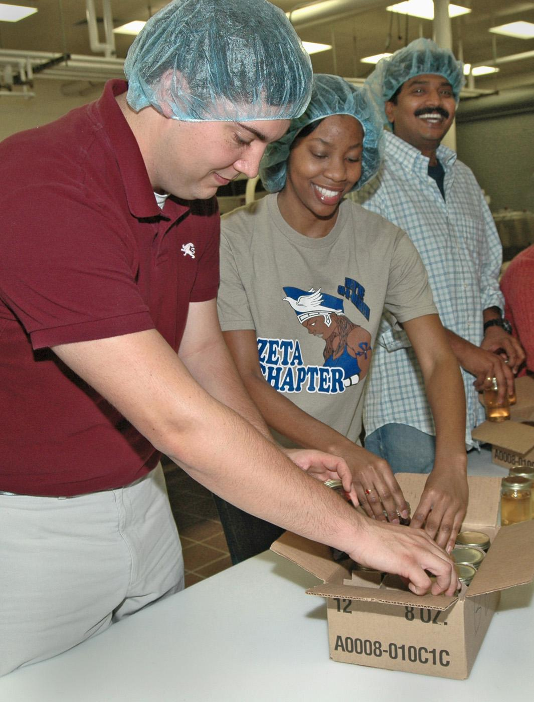 Mississippi State University food science club members, from left, Tony Garcia of Brandon, Gabrielle Bryant of Vicksburg and V. J. Radhakrishnan of India pack jars of muscadine jelly they made for area food pantries. (Photos by Patti Drapala)
