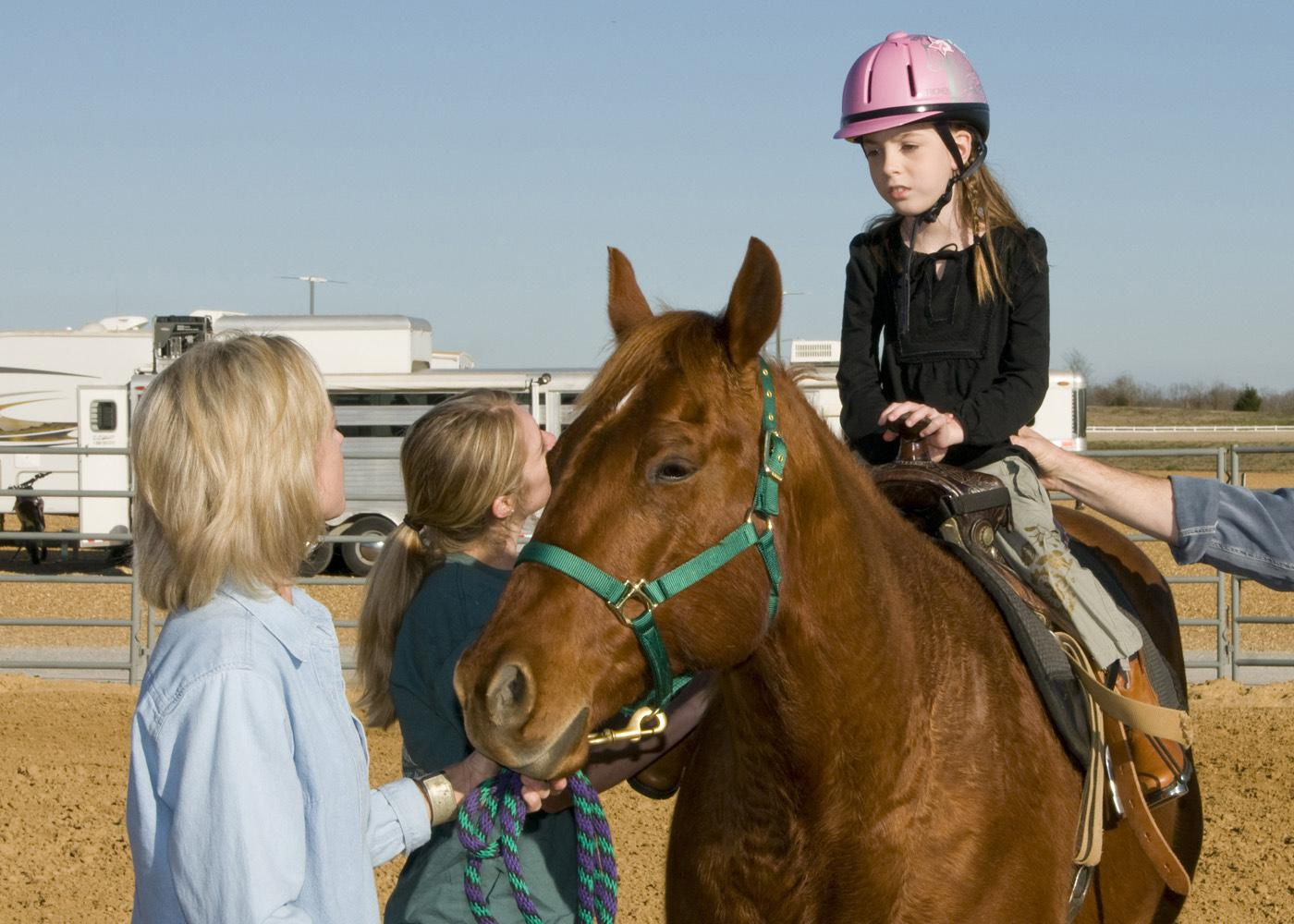 Mary Riley, coordinator for Mississippi State University's 4-H therapeutic riding program, and volunteer Shanna Holder, talk to 9-year-old Elizabeth Howard of Columbus as she sits atop her favorite horse, Bob. Howard's parents, Tommy and Brenda, are donating funds to construct a new therapeutic activity center in West Point. (Photo by Marco Nicovich)