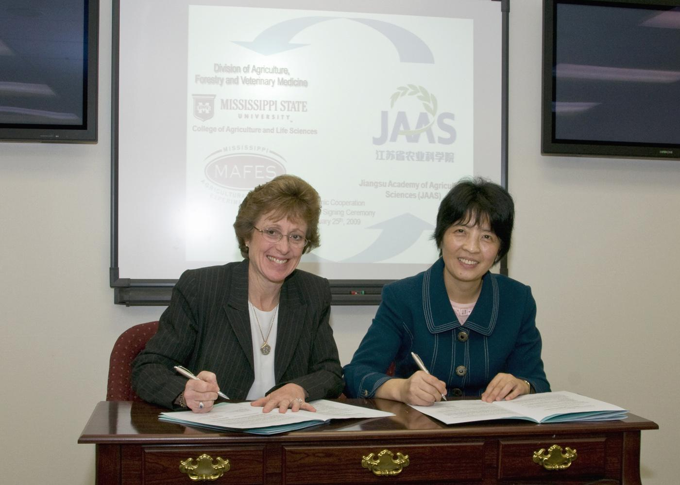 Melissa Mixon, left, and Xiaoxi Lu recently signed a five-year general agreement for academic cooperation between Mississippi State University and China's Jiangsu Academy of Agricultural Sciences. (Photo by Marco Nicovich)