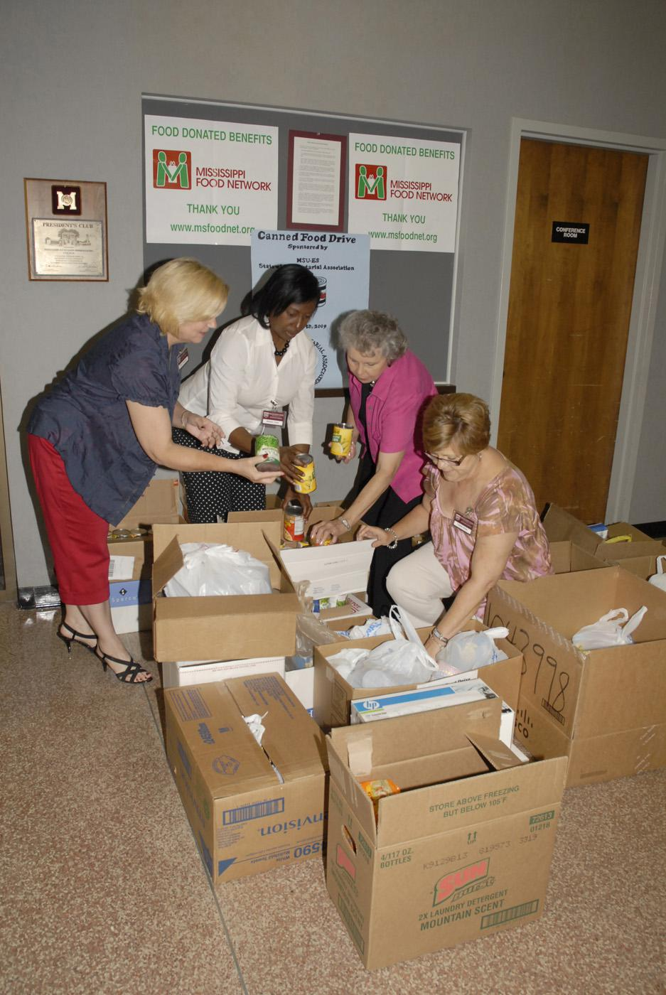 Mississippi Extension office associates Joyce Thompson of Oktibbeha County, Barbara Curry of the Northeast District office, Mary Minor of Marshall County and Colleen Butler of Scott County sort through hundreds of food items collected during their 2009 state meeting. (Photo by Linda Breazeale)