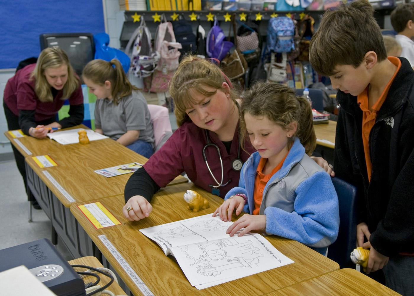 MSU veterinary student Shannon Vawter of Horn Lake works with third grade Starkville Academy students Carly Smith and Montana Brasher while MSU student Katie Ebers of Jackson (background) spends a moment with elementary student Mallory Barber. (Photo by Tom Thompson)