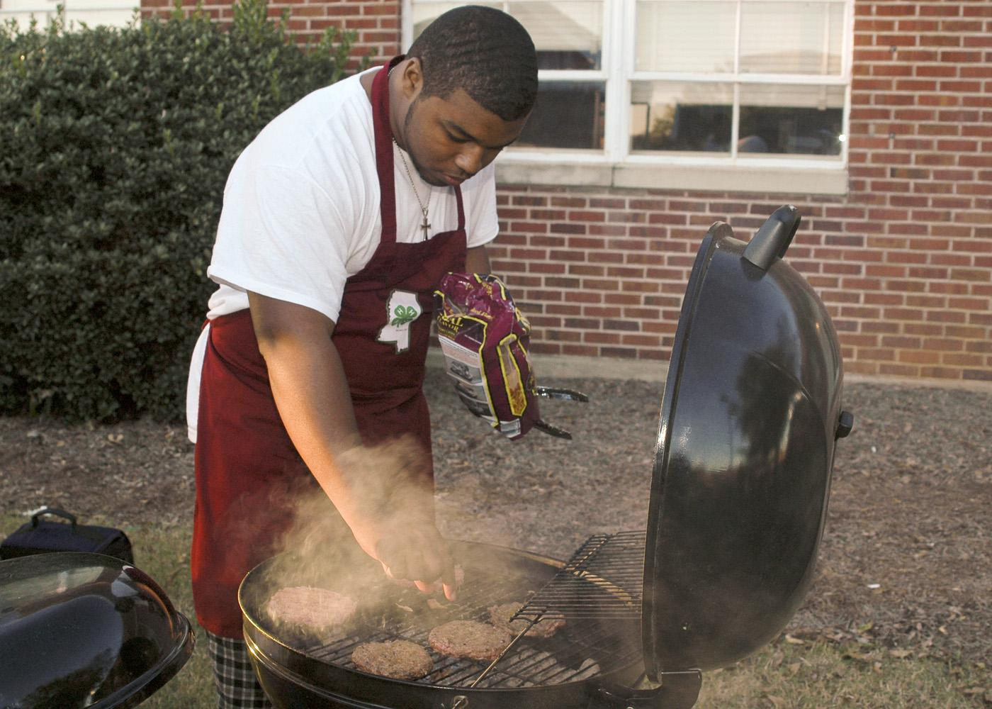 Mississippi State University Collegiate 4-H member Billy Hudson, 19, of Greenwood tries his hand at grilling during one of the club's recent football tailgates. While club members often get together to socialize, they make community service a priority. (Photo by Patti Drapala)