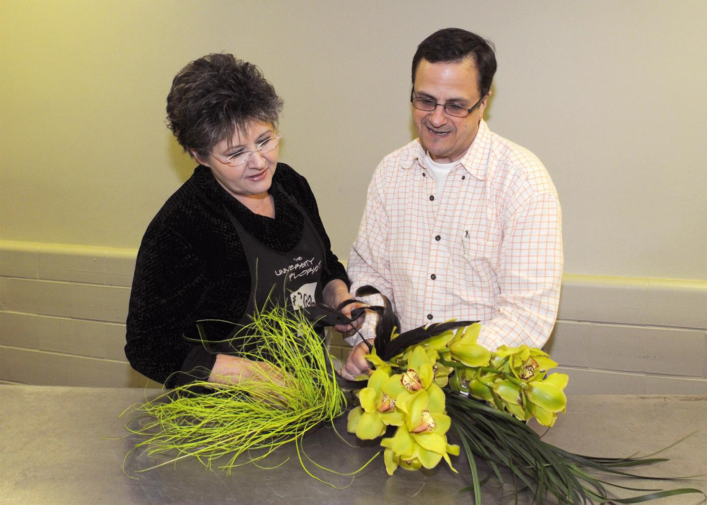 Mississippi State University florist manager Lynette McDougal and horticulture professor Jim DelPrince create a unique wedding arrangement of cymbidium orchids, lily grass, bear grass and feathers. (Photo by Kat Lawrence)