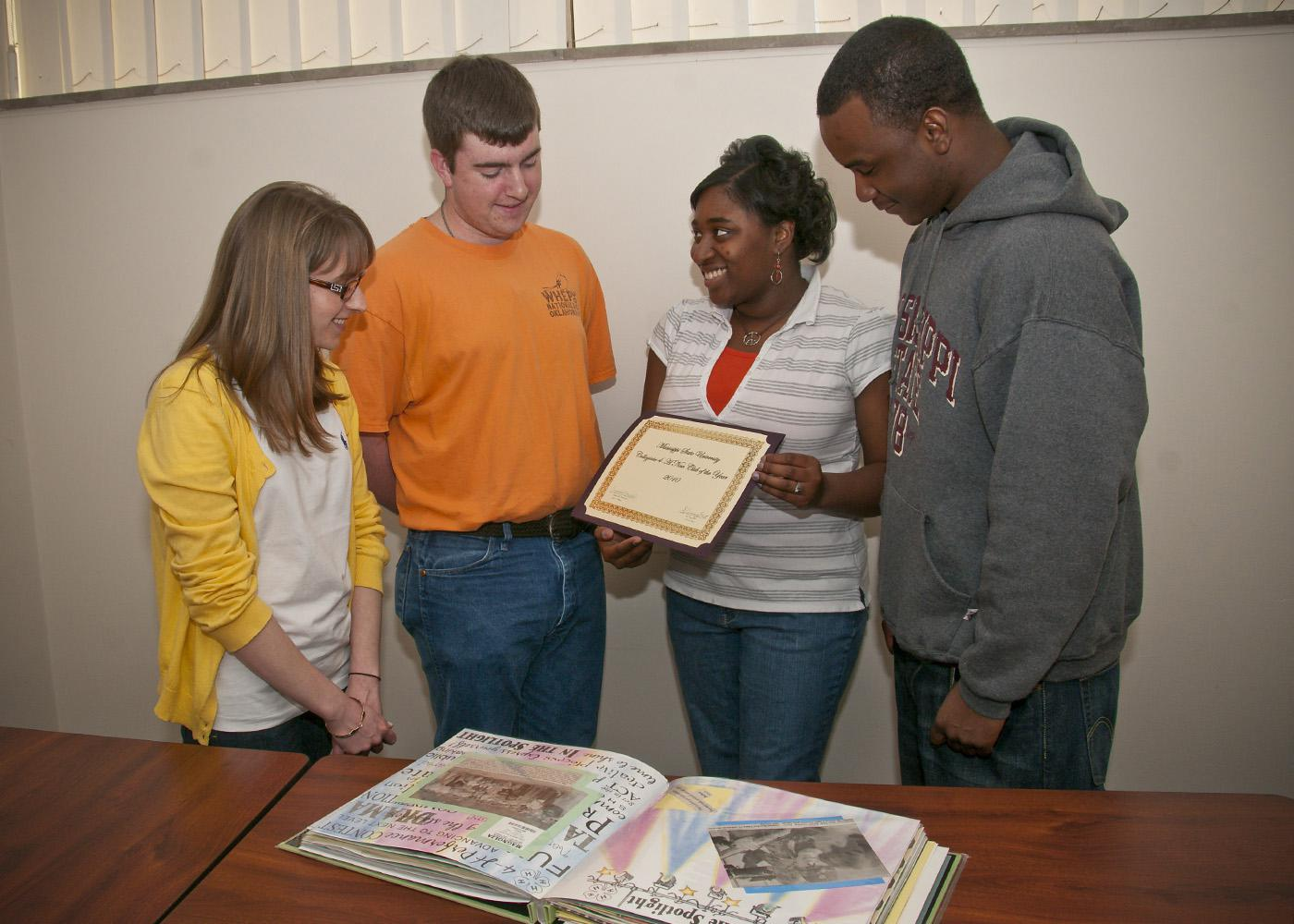 Looking over their winning application for national recognition are Mississippi State University Collegiate 4-H'ers, from left, Savannah Duckworth of New Albany, Stuart Wright of Columbus, Brittany Reed of Greenwood and Shad Benn of Hattiesburg. (Photo by Scott Corey)