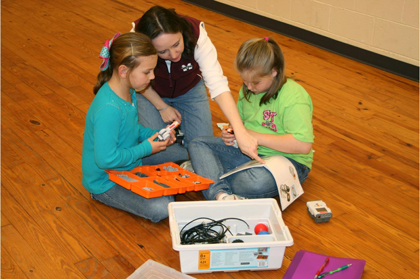 Kaitlyn Plance, left, and Jordan Jackson, right, work to build a robot with Amy Walsh, Amite County 4-H Agent. The youth are learning science, technology and engineering through the 4-H robotics program. (Photo by Mariah Smith)
