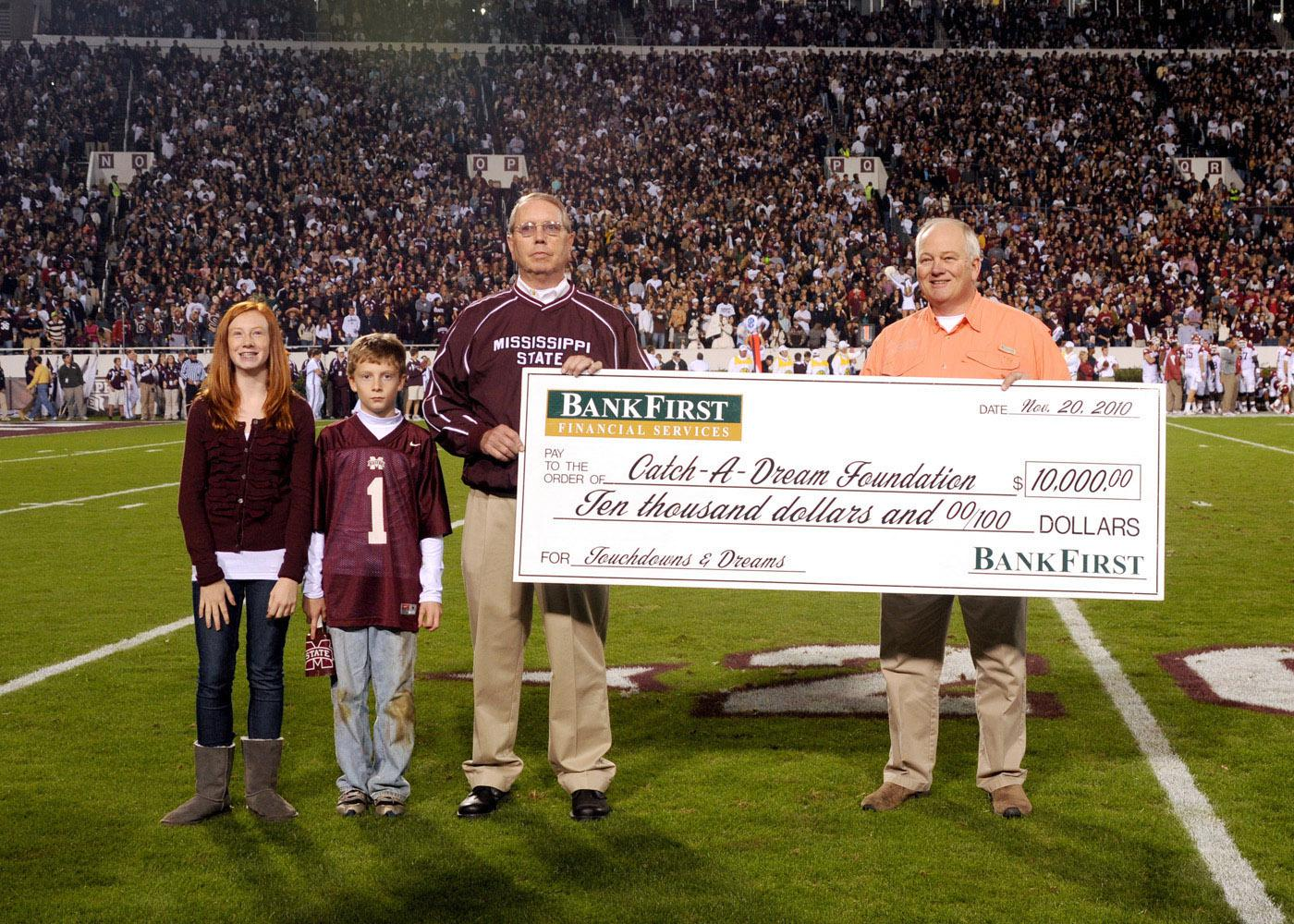 BankFirst made a donation to the Catch-A-Dream Foundation every time the Mississippi State University Bulldogs scored touchdowns. BankFirst's Jerry Wilson, left, presents a ceremonial check for $10,000 to Marty Brunson at the MSU-Arkansas game Nov. 20. Wilson is accompanied by his grandchildren, Mauri and Miller Wilson. (Photo by MSU Ag Communications/Kat Lawrence)