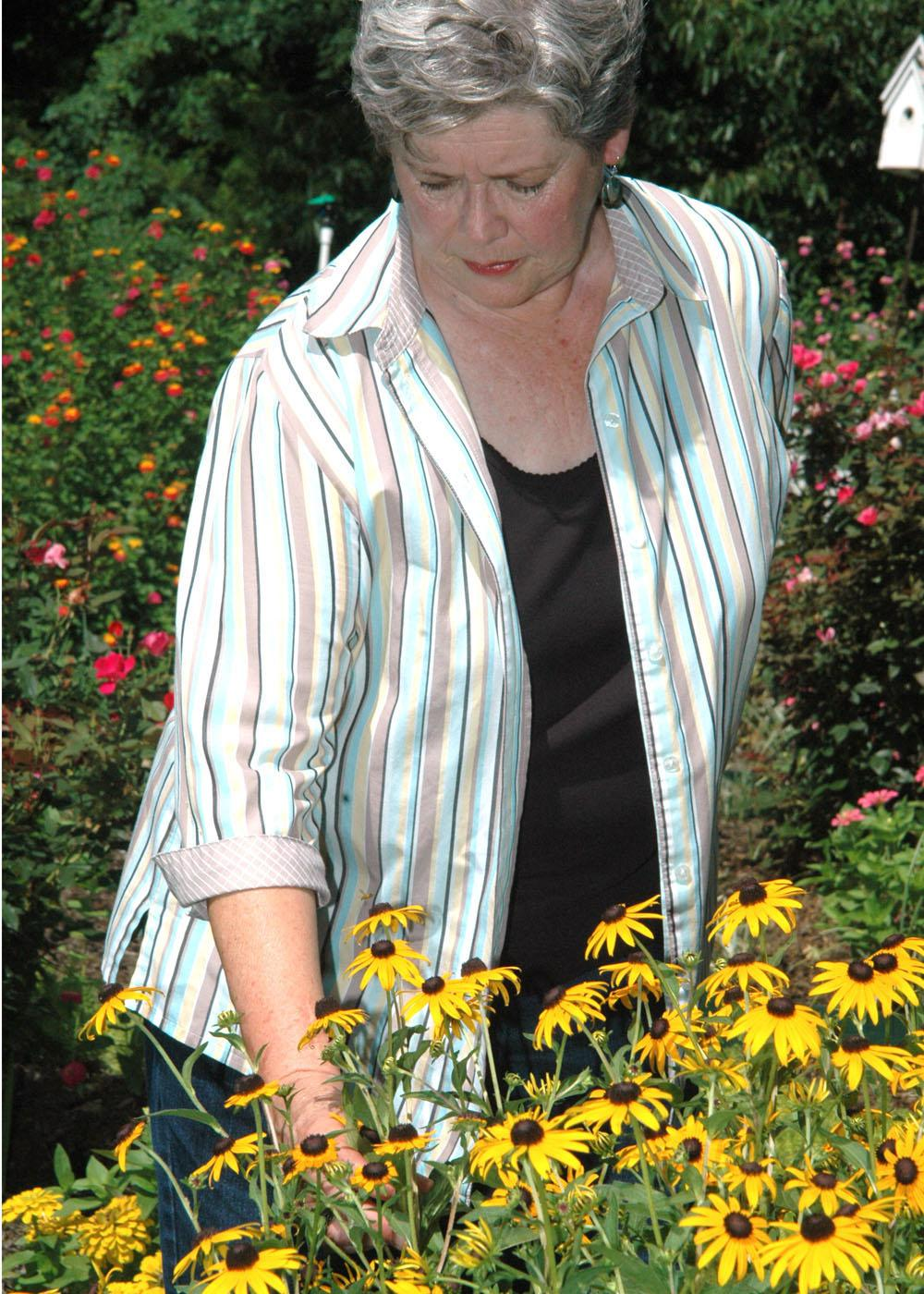 Rankin County Master Gardeners president Nellie Axley of Brandon admires the refurbished flower bed the group created for the local Extension office landscape.