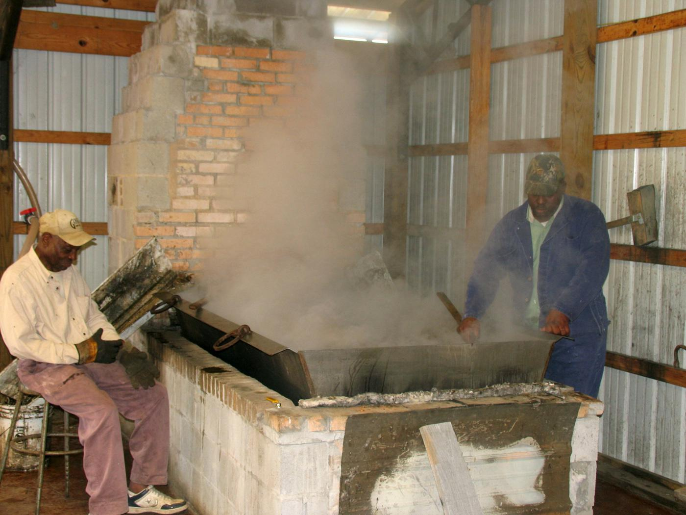Hosea Brown, right, cooks down sugar cane syrup to molasses the old-fashioned way over a wood fire in his family business in Jefferson Davis County. Family friend Joe Norwood helps with the work at My Paw Paw's Ole Fashion Molasses in New Hebron. (Photo by Prentiss Headlight/Shirley Burnham)