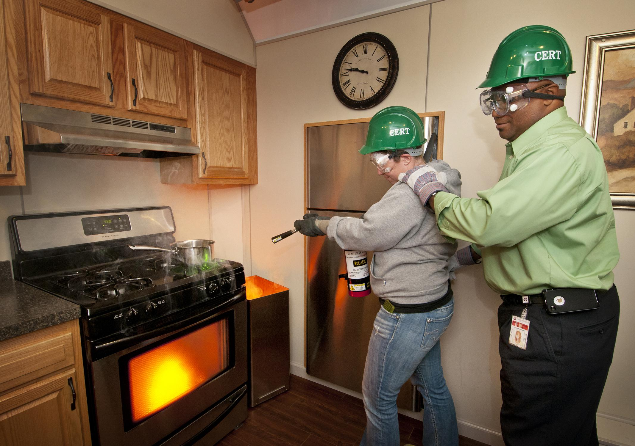 Donna Adams (left), area coordinator for Mississippi State University's student housing, and Calvin Mosley, associate director of student housing, extinguish a simulated fire in a trailer specifically designed for teaching fire control skills. Adams and Mosley are part of a group of 28 faculty and students who participated in MSU's Campus Community Emergency Response Team training. The CERT program educates people about disaster preparedness for hazards that may impact their area. The Nov. 8 training was ad
