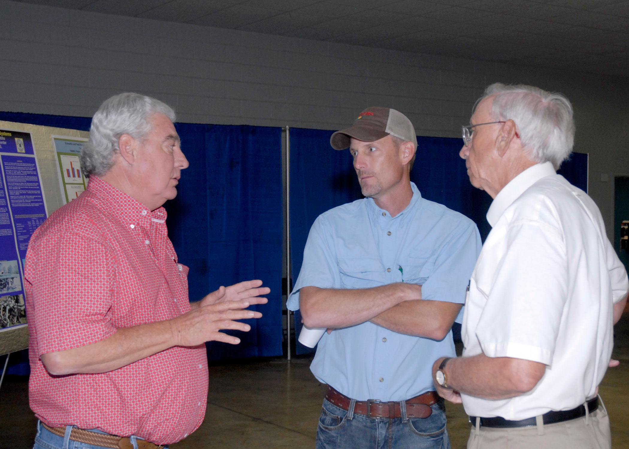 From left, Roger Worsham, a tillage equipment vendor, reviews tillage options with Glenn Gilmer, a farmer from Caledonia, and Normie Buehring, a research professor with the Mississippi Agricultural and Forestry Experiment Station. The three were taking part in the North Mississippi Row Crops Field Day Aug. 9, 2012, at the North Mississippi Research and Extension Center in Verona. (Photo by MSU Ag Communications/Linda Breazeale)