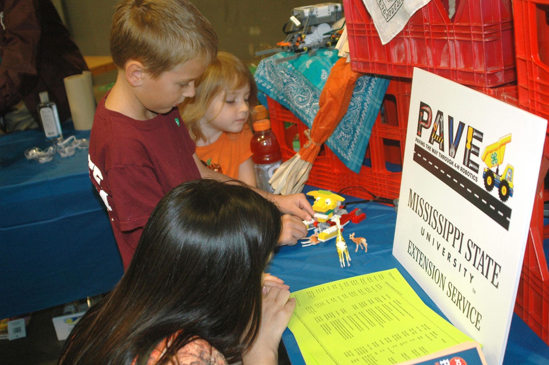 Monica Morel, Hancock County robotics club volunteer leader, helps Luke and Rebekah Schilling of Oktibbeha County with a robot during 4-H Day at the Mississippi State Fair in Jackson on Oct. 13. The robotics exhibit was one of several hands-on science activities available to visitors. (Photo by MSU Ag Communications/Susan Collins-Smith)