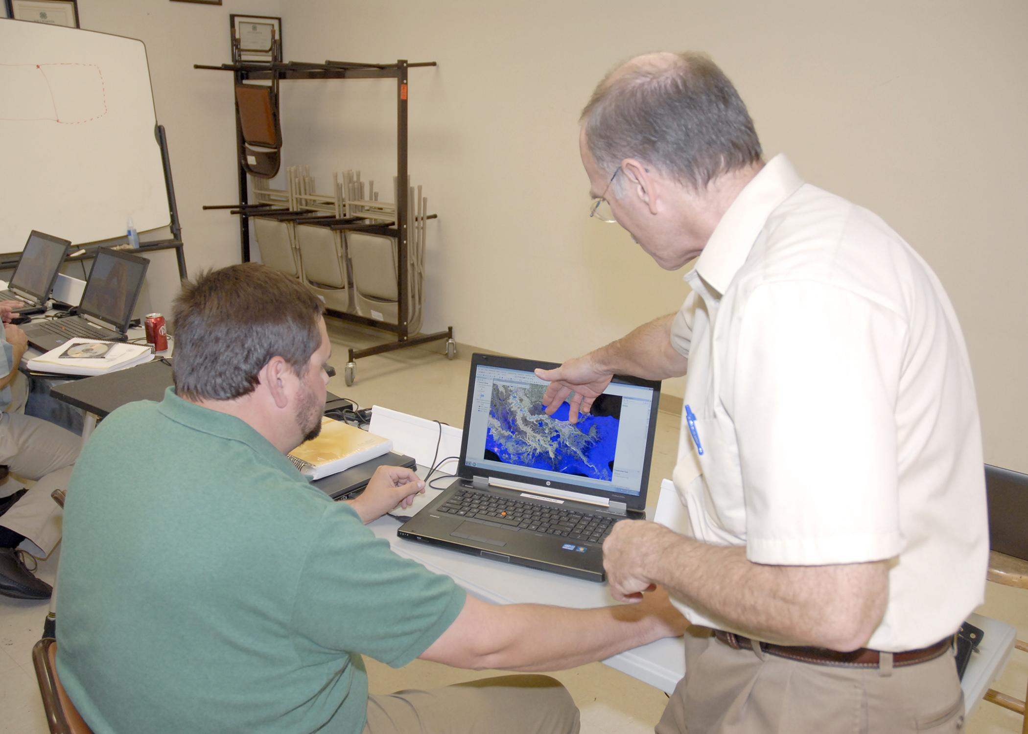 Jim Davis of Olive Branch, left, with the Mississippi Department of Transportation, learns how to use new software from Scott Samson, professor with the Extension Service and the Geosystems Research Institute at Mississippi State University, during a class in Hernando on Oct. 17, 2012. (Photo by MSU Ag Communications/Linda Breazeale)