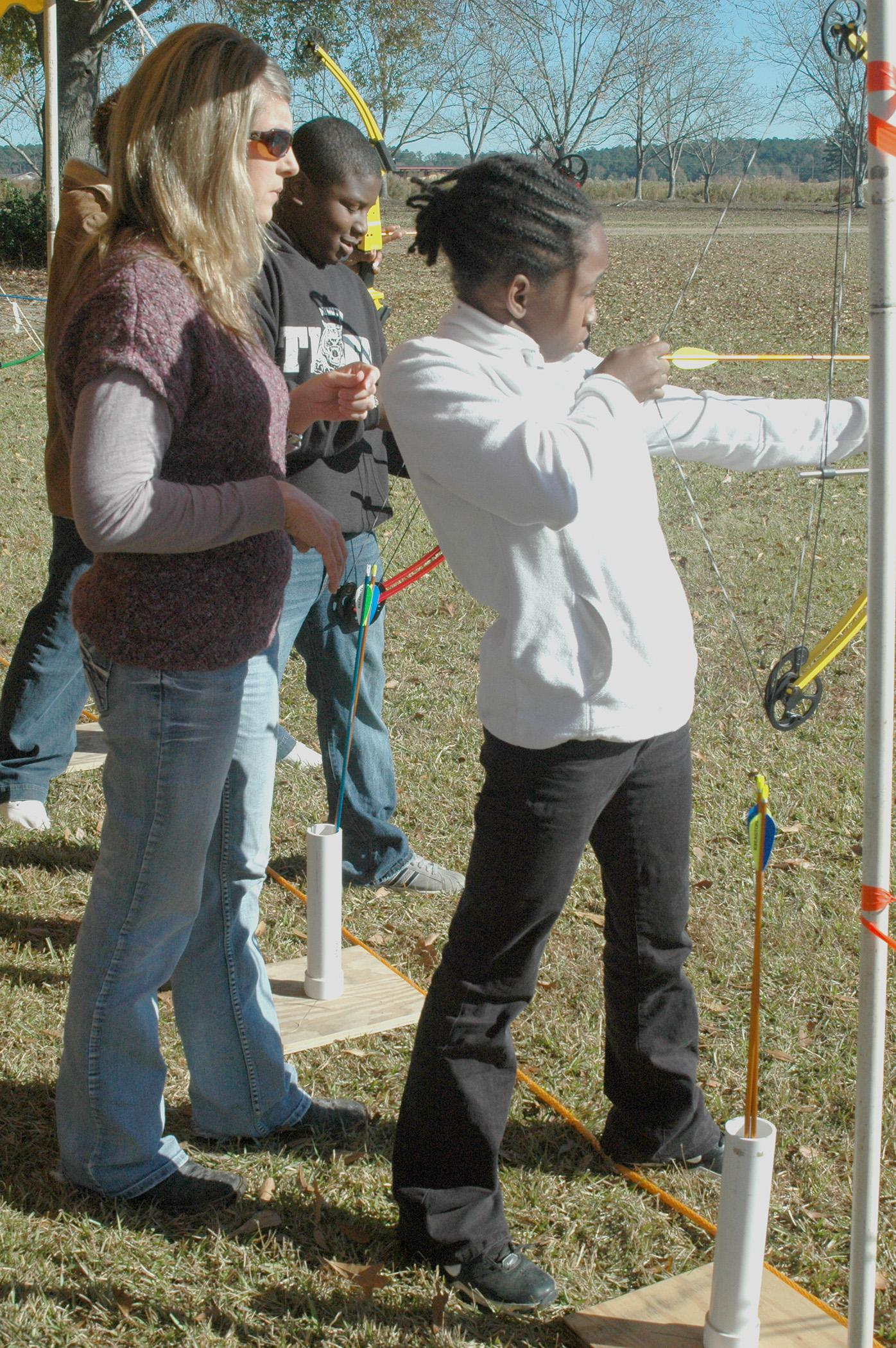 Leanne Wagner McGee, Newton County Extension agent, looks on as Nia McCalphia and Jemariaus Ford prepare to shoot arrows at their targets during the Wildlife Youth Day at the Coastal Plains Experiment Station Nov. 16. (MSU Ag Communications/Susan Collins-Smith)
