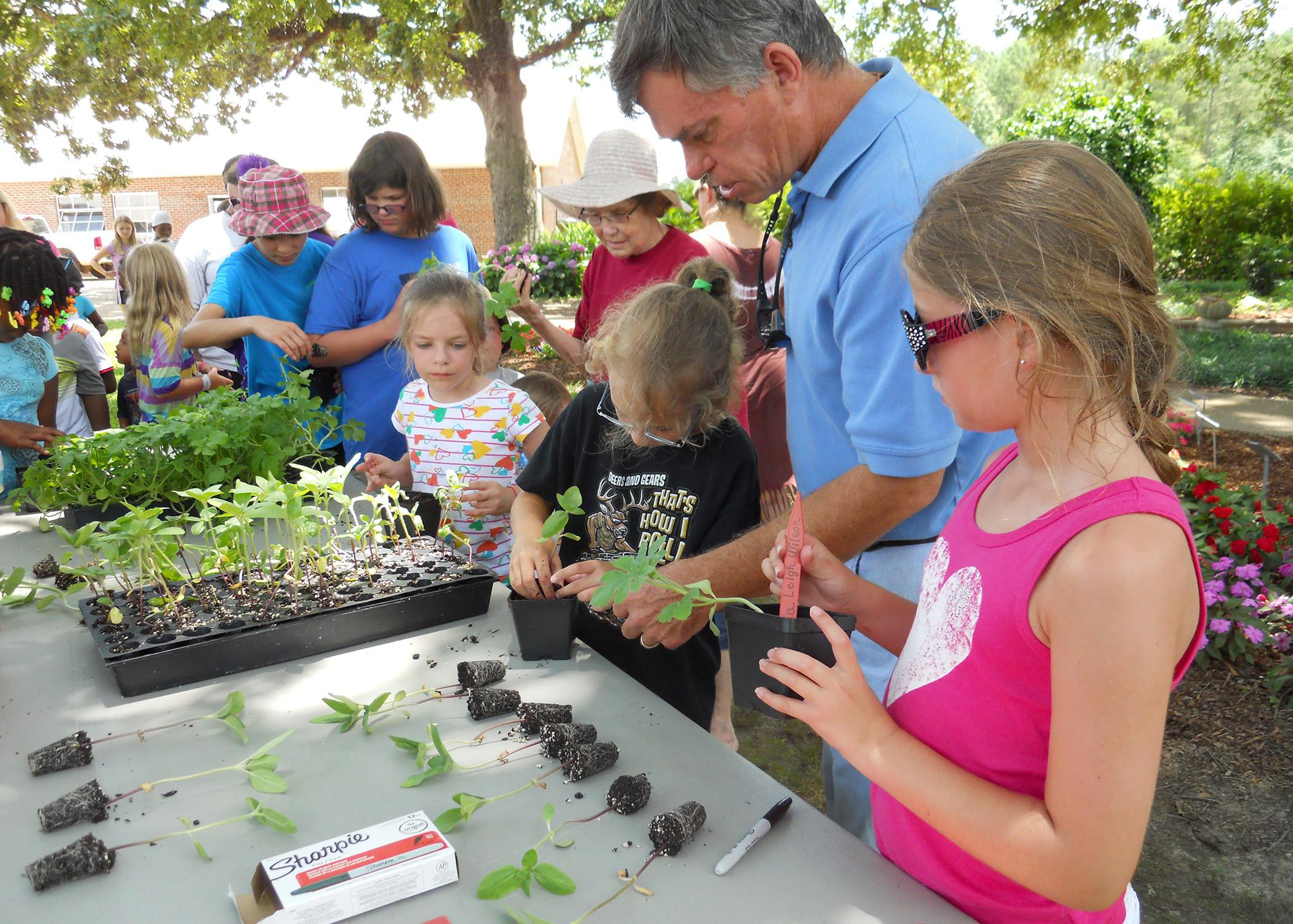 Bill Evans, center, helps Bayleigh Newman, left, and Olivia Leigh Williams, right, plant their watermelon seedlings at Mississippi State University's Truck Crops Station June 12. Employees at the station held a short program on gardening to complement the Dig into Reading theme of this year's statewide library summer reading program. (Photo by MSU Ag Communications/Susan Collins-Smith)