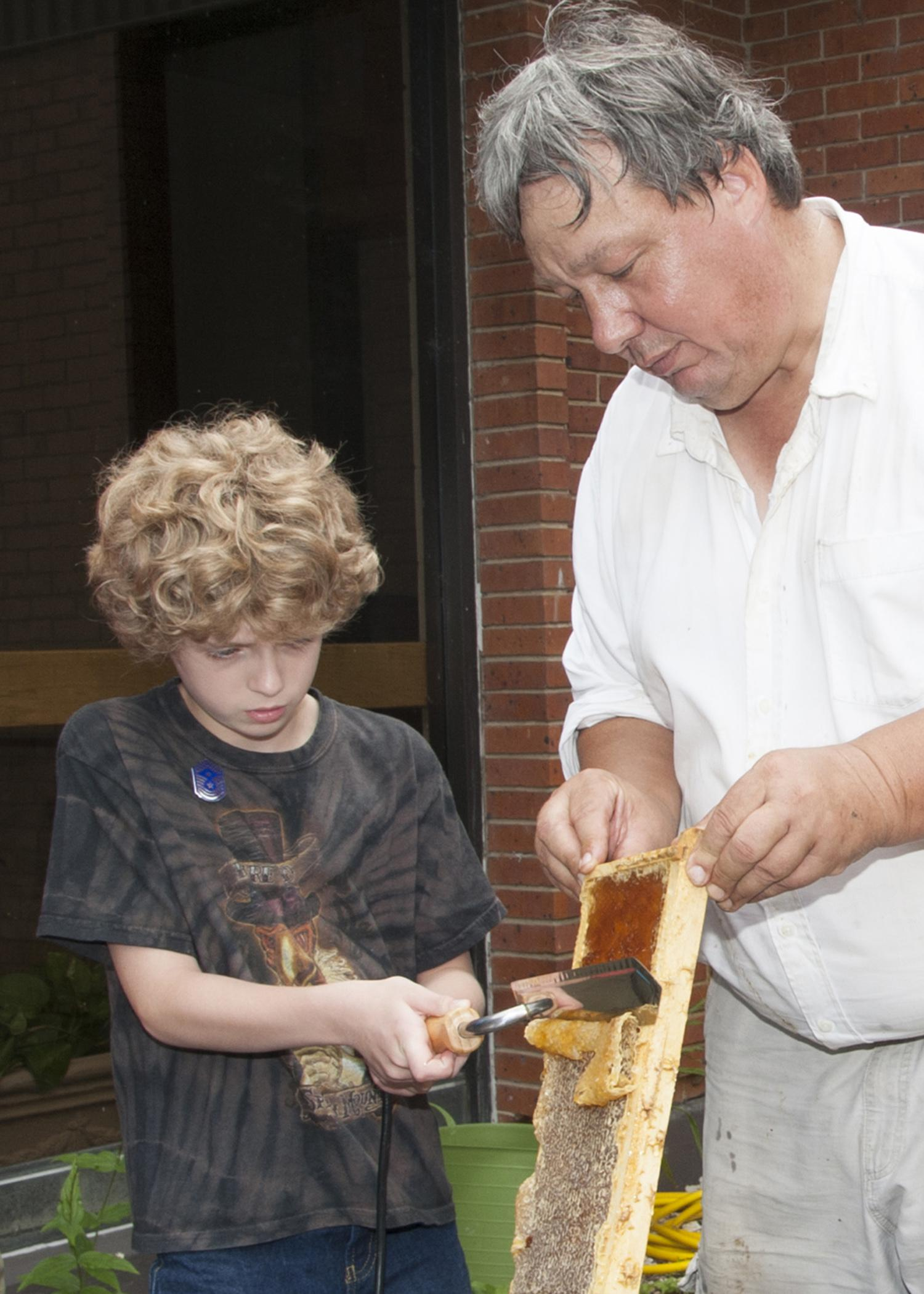 MSU Extension entomologist Jeff Harris holds a bee frame while Emmett King, 10, carefully harvests the honey. Beekeeping was one topic covered in Mississippi State University's 20th annual Bug and Plant Camp. (Photo by MSU Ag Communications/Kat Lawrence)