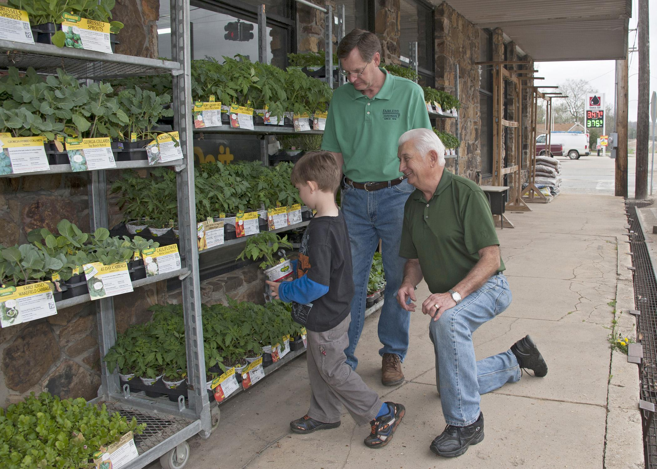 Jerry Don Keith, Tishomingo County Master Gardener, right, helps his grandson Brooks Keith select tomato plants from James Tennyson's inventory at Fairless Hardware Co. in Tishomingo on April 3, 2014. (Photo by MSU Ag Communications/Kat Lawrence)