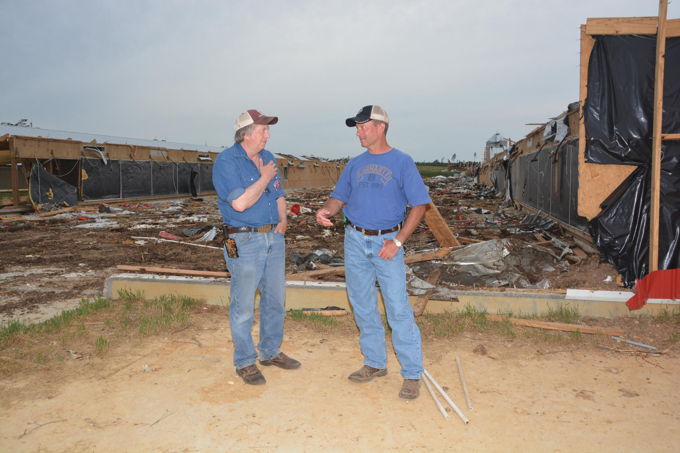 Mississippi State University Extension Service poultry specialist Tom Tabler, left, visits with Winston County poultry grower Tim Hobby on May 8, 2014. Hobby lost 10 broiler houses in the April 28 tornado. (Photo by MSU Ag Communications/Linda Breazeale)