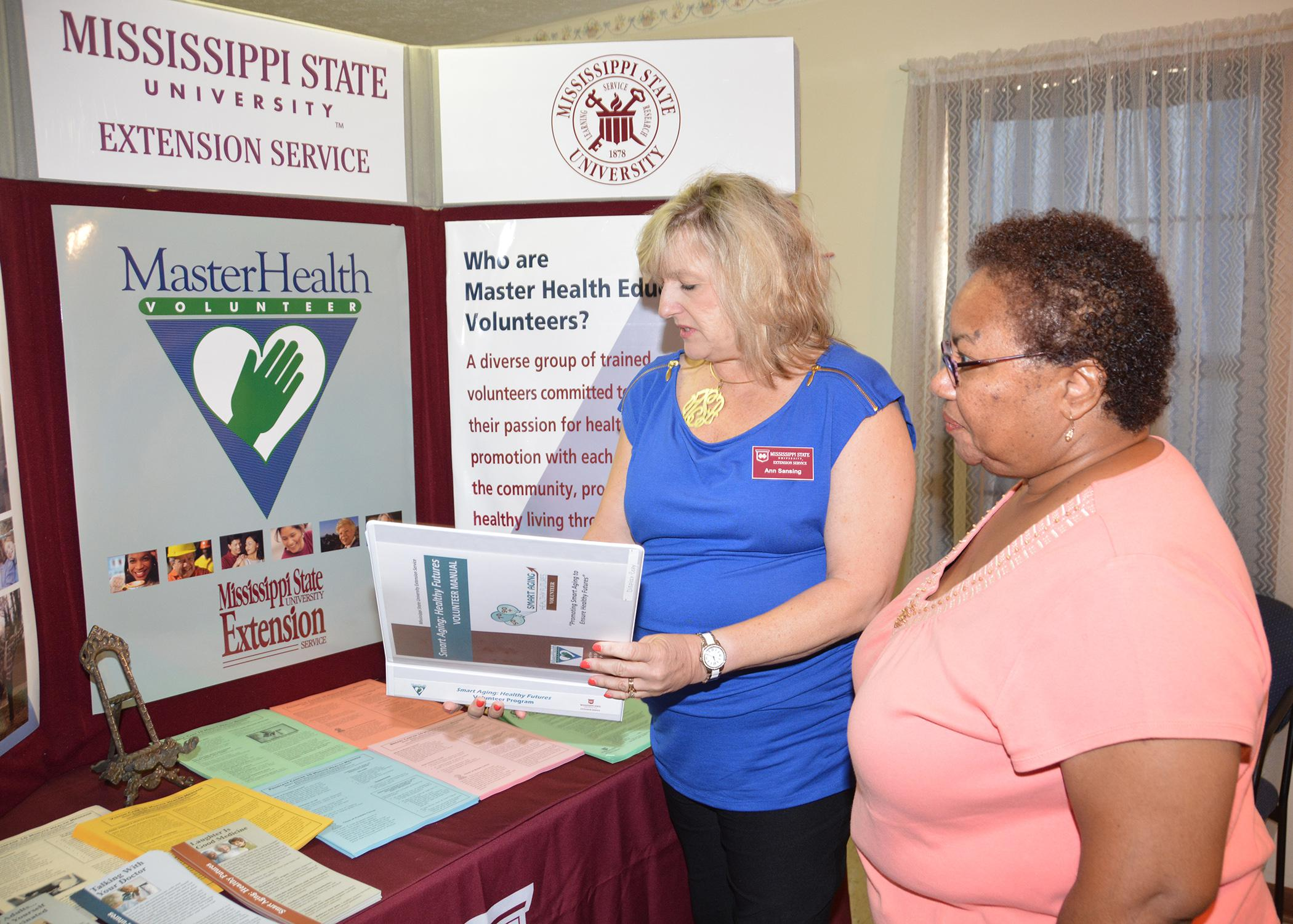 Mississippi State University Extension community health coordinator Ann Sansing reviews some of the Master Health Volunteer educational material with Annie Williams at the one-year anniversary celebration of the John Wesley Health Education Center in Durant, Mississippi, on July 25, 2014. (Photo by MSU Ag Communications/Linda Breazeale)
