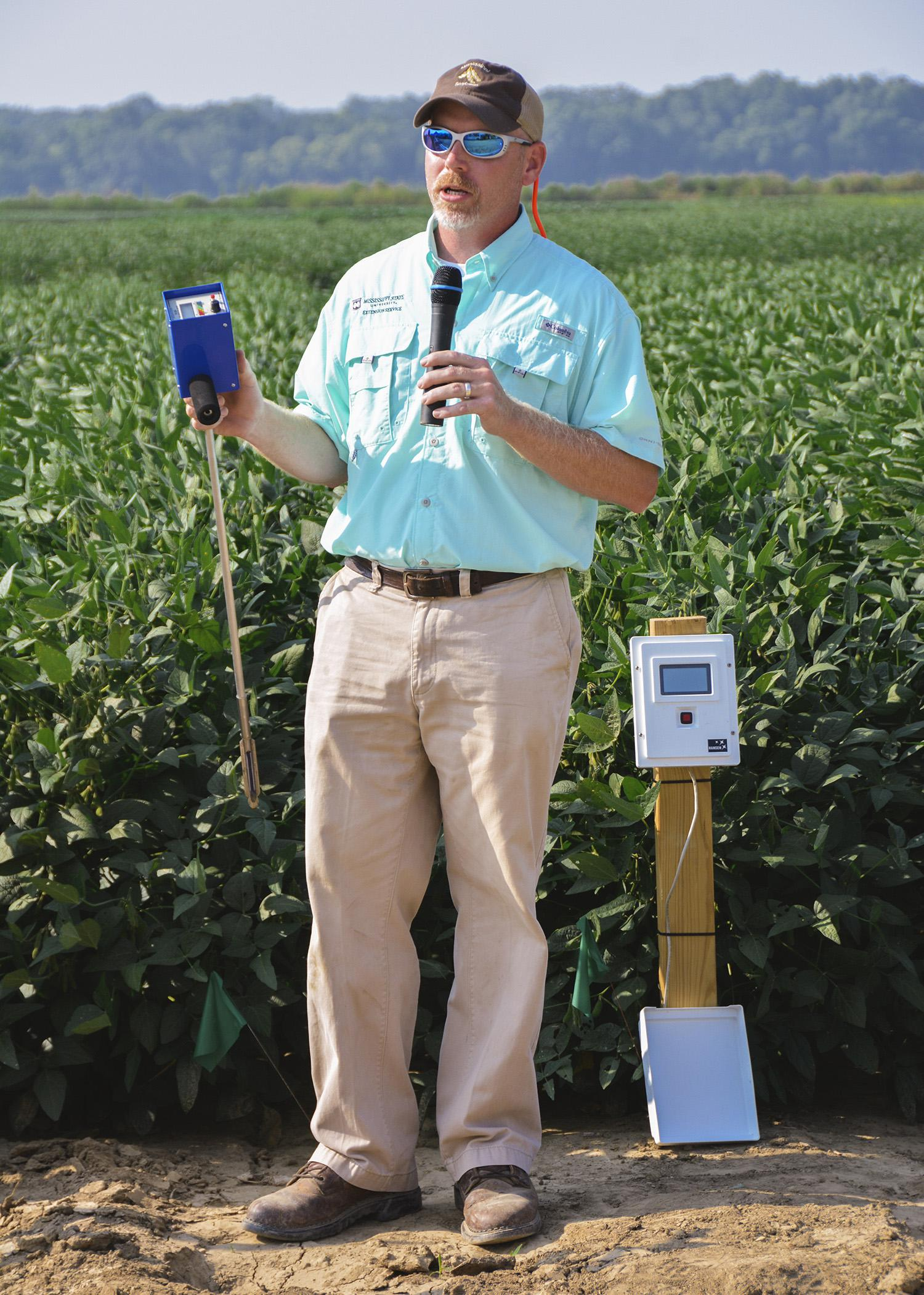 Jason Krutz, an irrigation specialist at the MSU Delta Research and Extension Center, reviews different types of moisture meters available to help farmers determine irrigation timing. Krutz took part in the North Mississippi Research and Extension Center's Agronomic Row Crops Field Day in Verona, Mississippi, on Aug. 7, 2014. (Photo by MSU Ag Communications/Linda Breazeale)