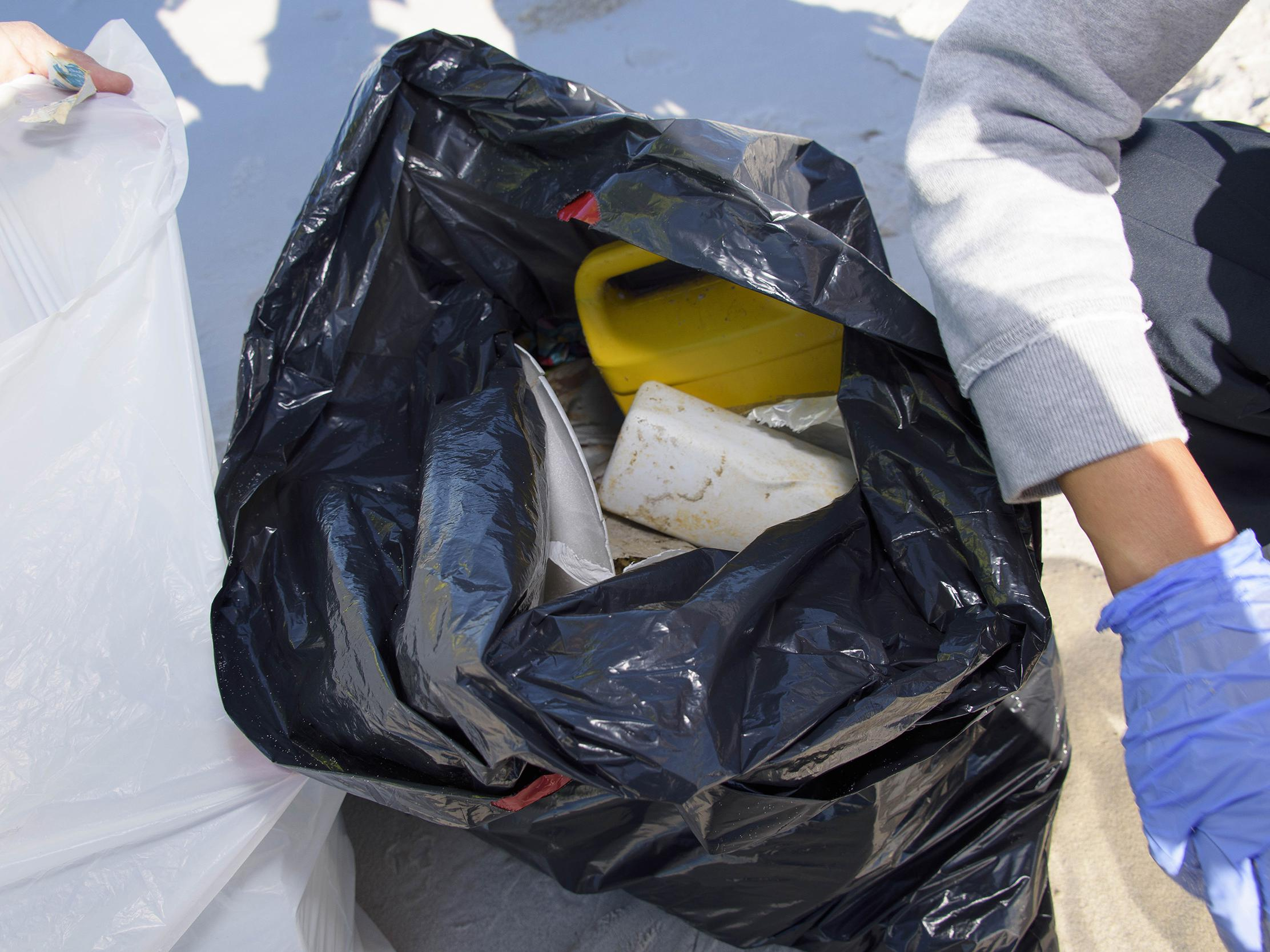 Plastic debris is seen in an open black trash bag sitting on the beach at the 2016 Mississippi Coastal Cleanup.