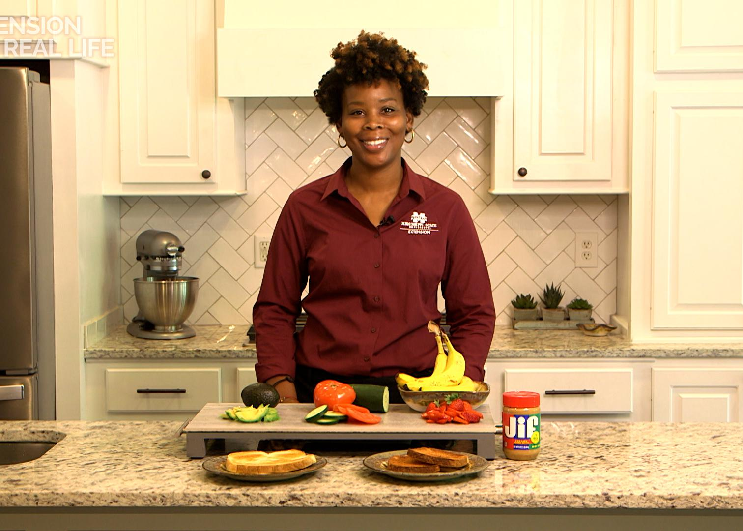 A woman stands behind a kitchen counter of breakfast toast and toppings.