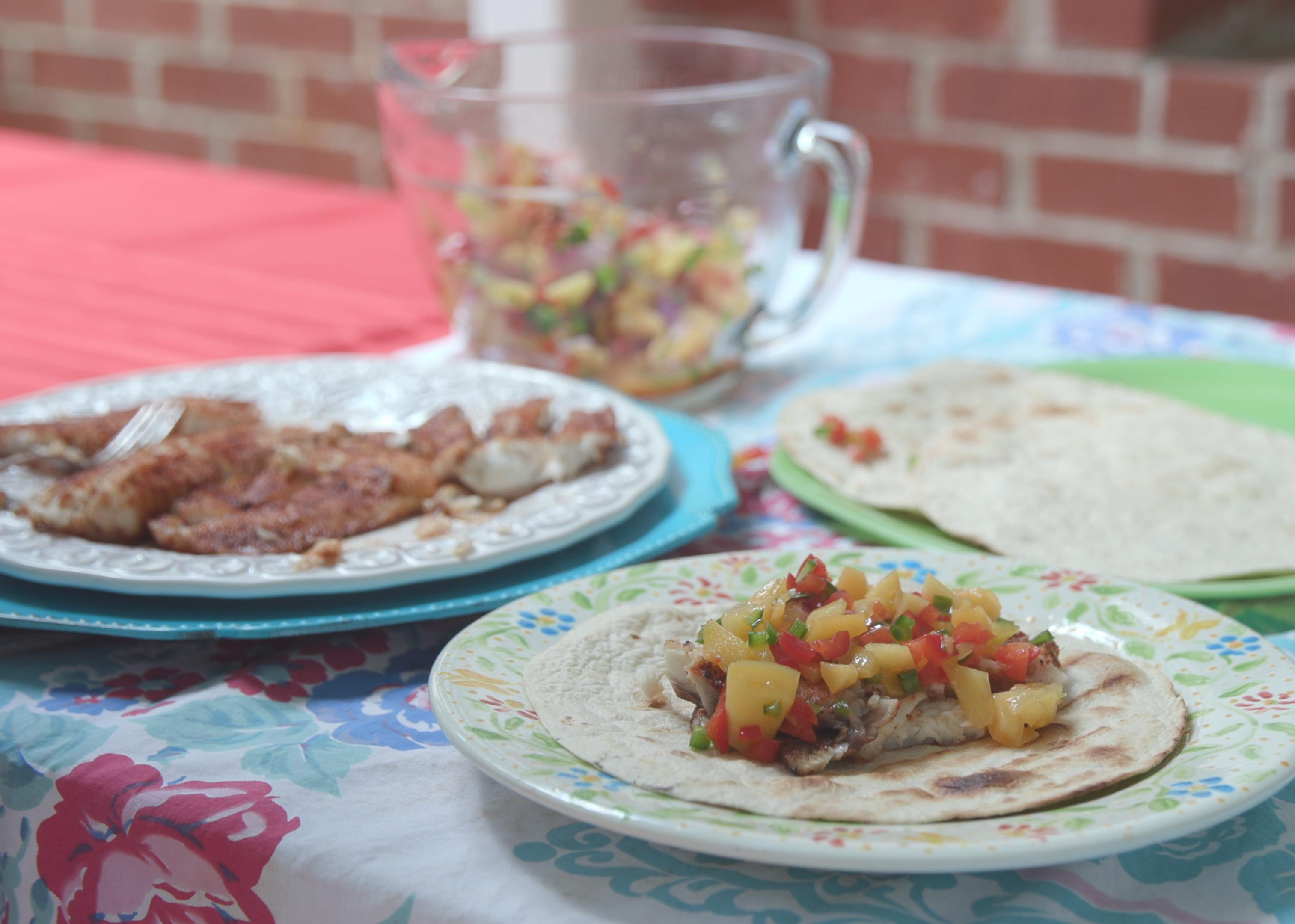 Three plates with tortillas, fish, and a completed grilled fish taco with peach salsa on a picnic table.