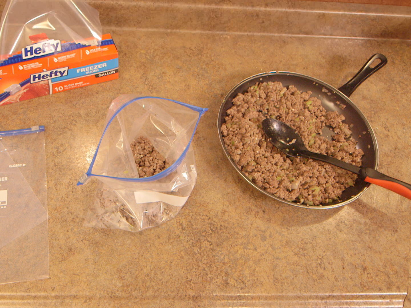 Browned ground beef, chopped onions, celery, and garlic in a non-stick skillet ready to spoon into individual freezer bags.