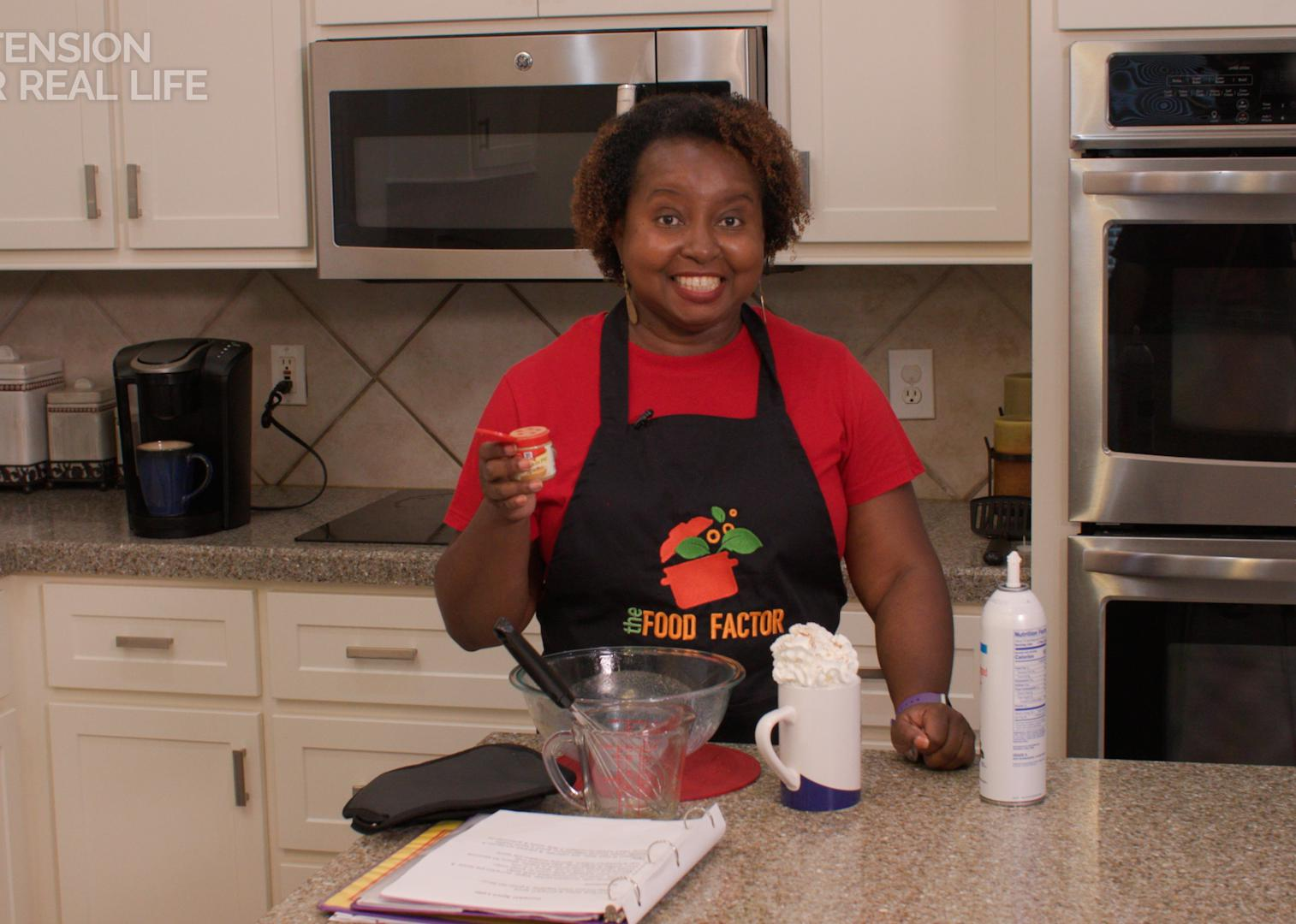 A woman stands at a kitchen counter with a latte.