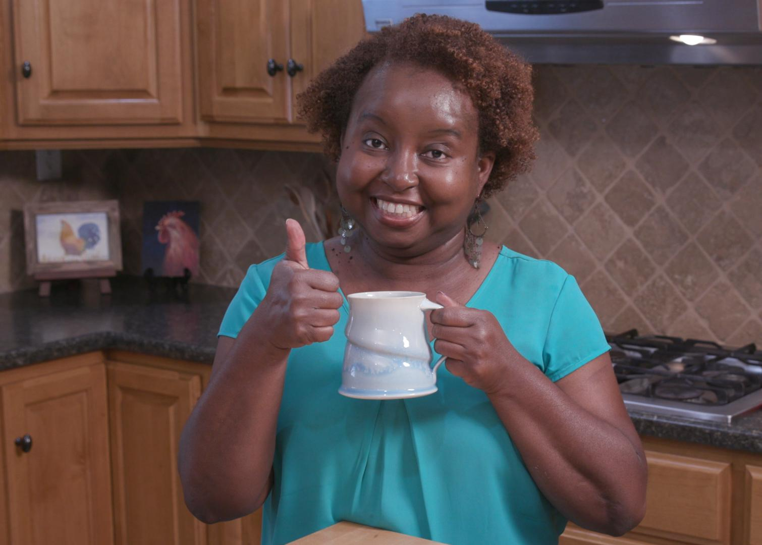 Food Factor host Natasha Haynes holds a mug of cocoa while standing in a kitchen