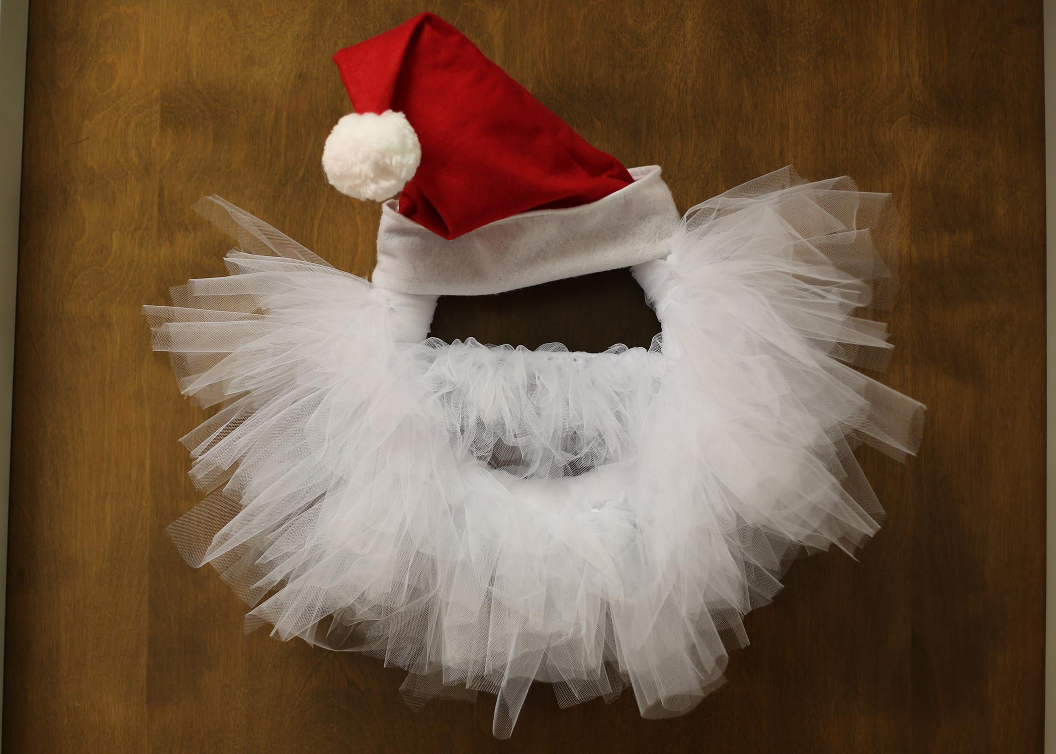 Wreath with Santa hat and white tulle shaped to look like a beard hanging on a wooden door.