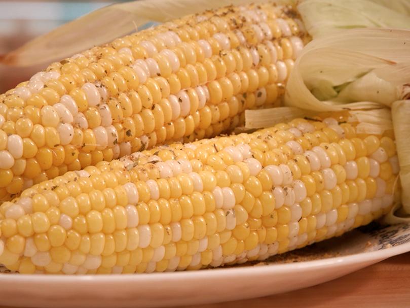 Two ears of seasoned grilled corn on a platter.