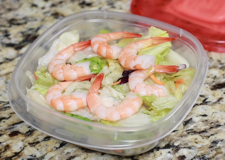A bowl of salad with shrimp on top.