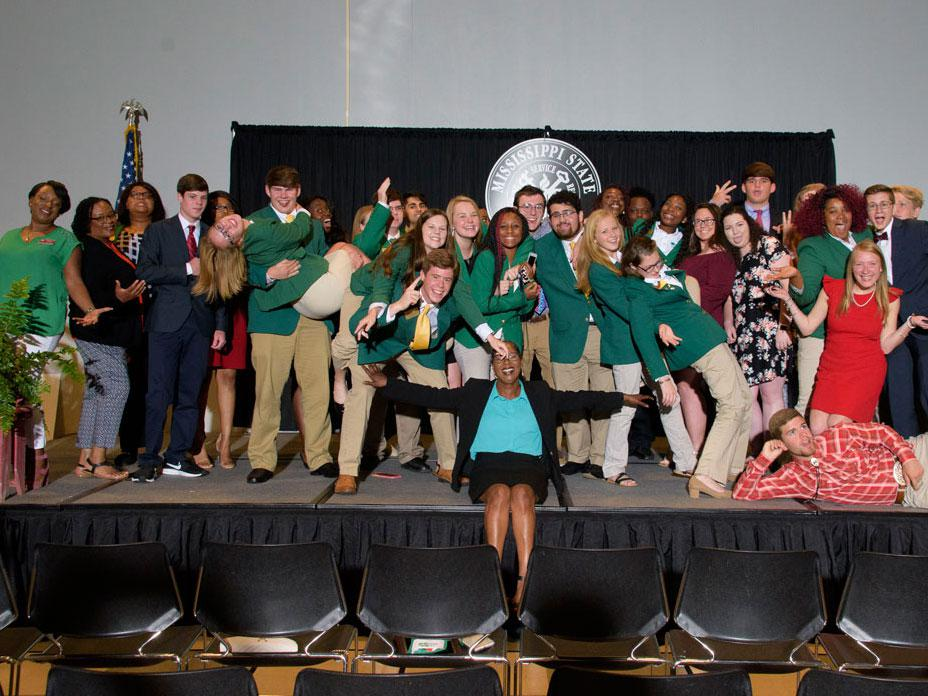 A group of teenagers posing on a stage.