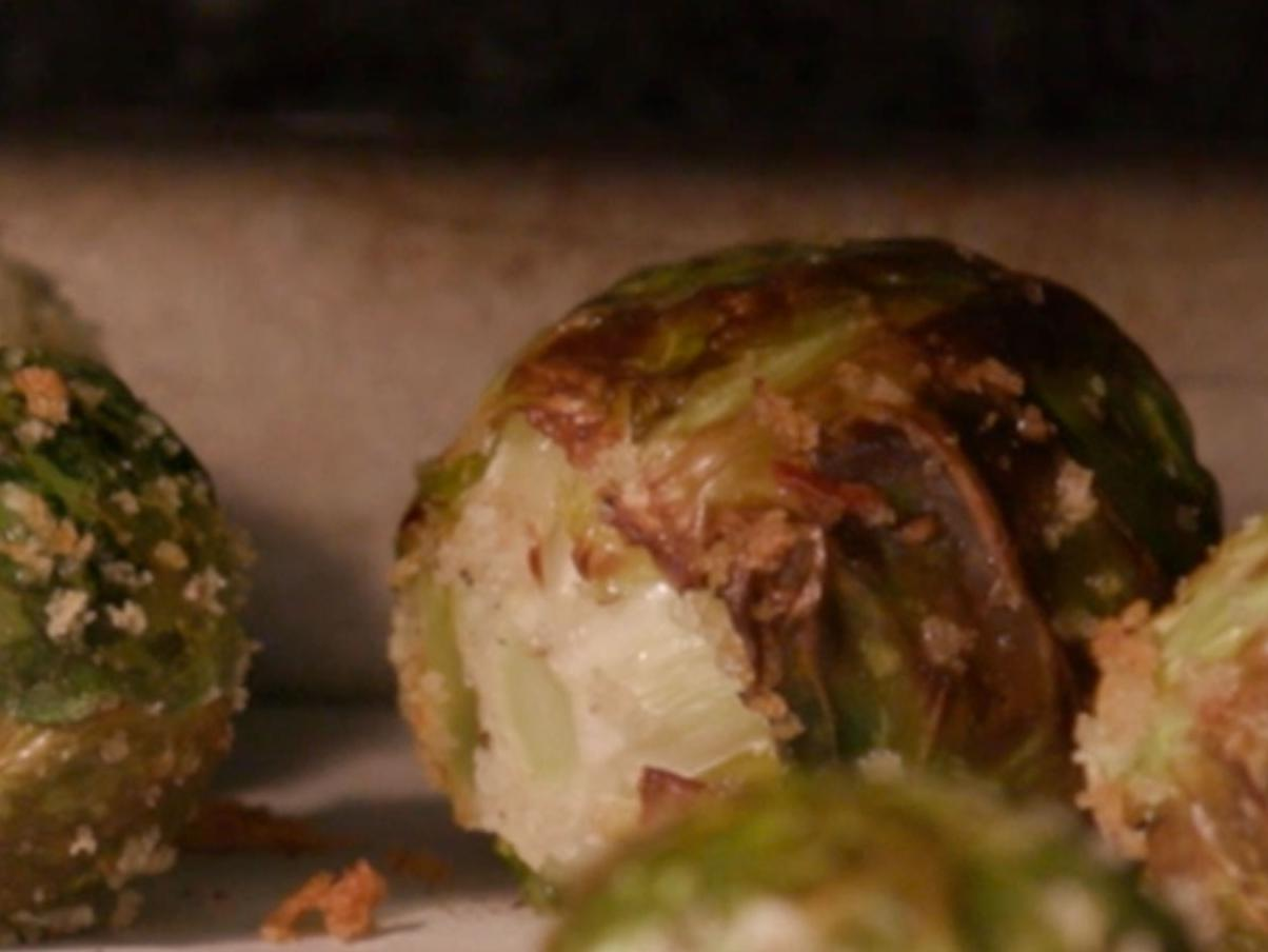 Close-up of roasted Brussels sprouts coated with Panko breadcrumbs on a sheet pan covered with parchment paper.