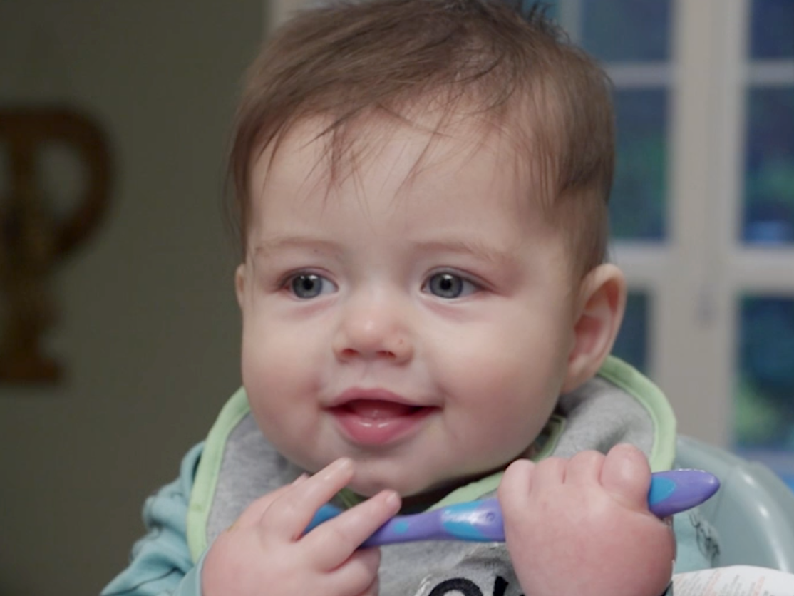 A 10-month-old baby eats homemade baby food.