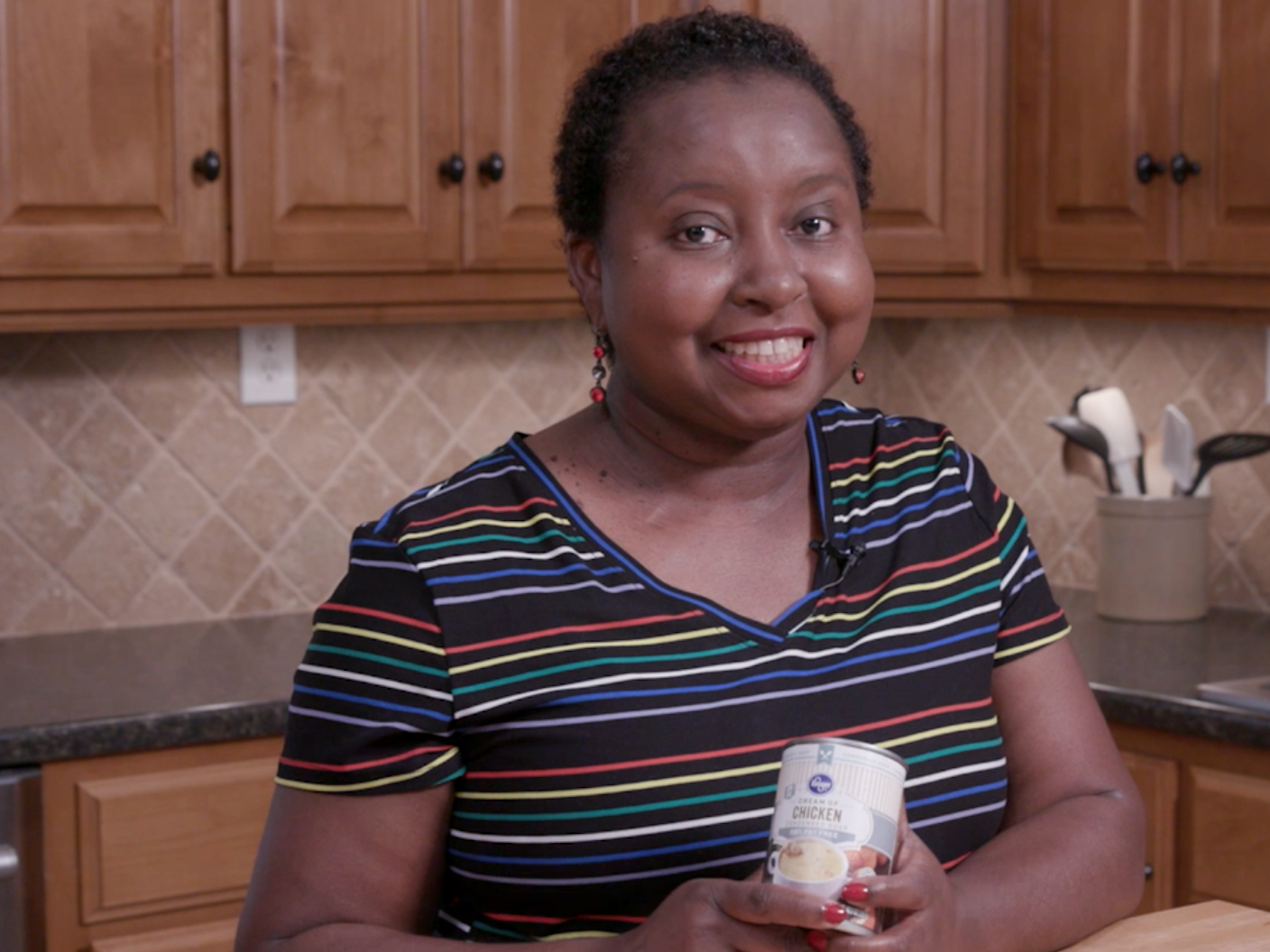 A woman stands in a kitchen while holding a can of reduced fat cream of chicken soup.